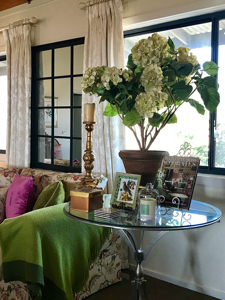 The colours I use are a reflection of my personality. Jewel tones of cerise pink and pretty green with touches of gold are both warm and glamorous. Classic cream curtains and walls provide a clean backdrop. The accessory of the large black mirror gathers the light and reflects the view.
