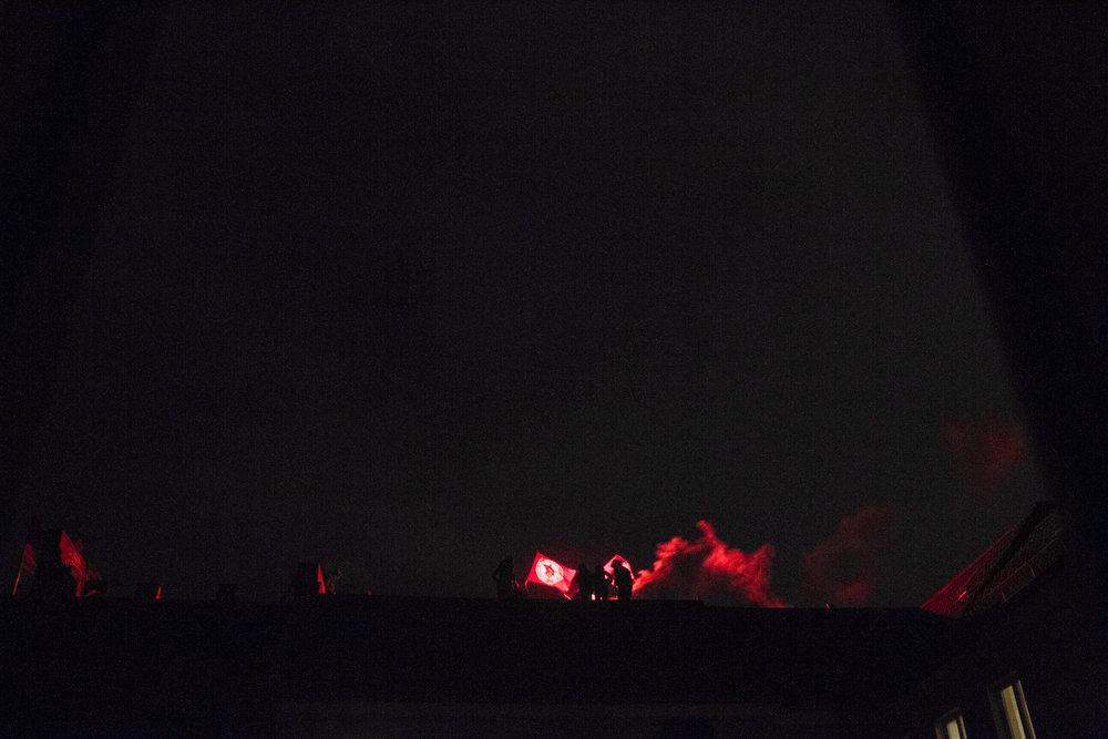 "November 21,  2014.  Residents of the ""Abstand"" squat light flares on the roof of Rigaer Straße 79 on the anniversary of the murder of Silvio Meier by Neo-Nazi's in 1992."
