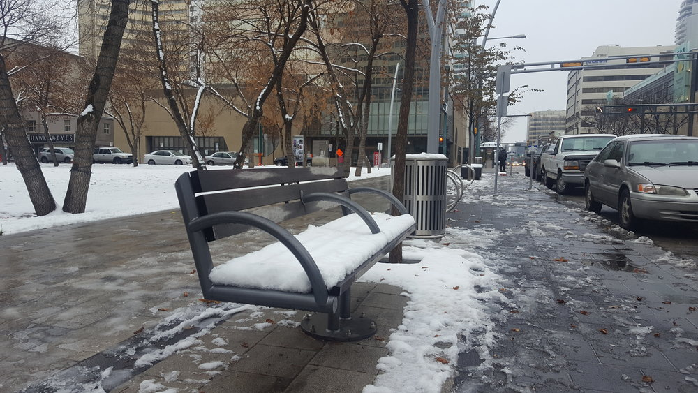 Image:A public bench on Jasper Avenue, with a metal bar in the centre.