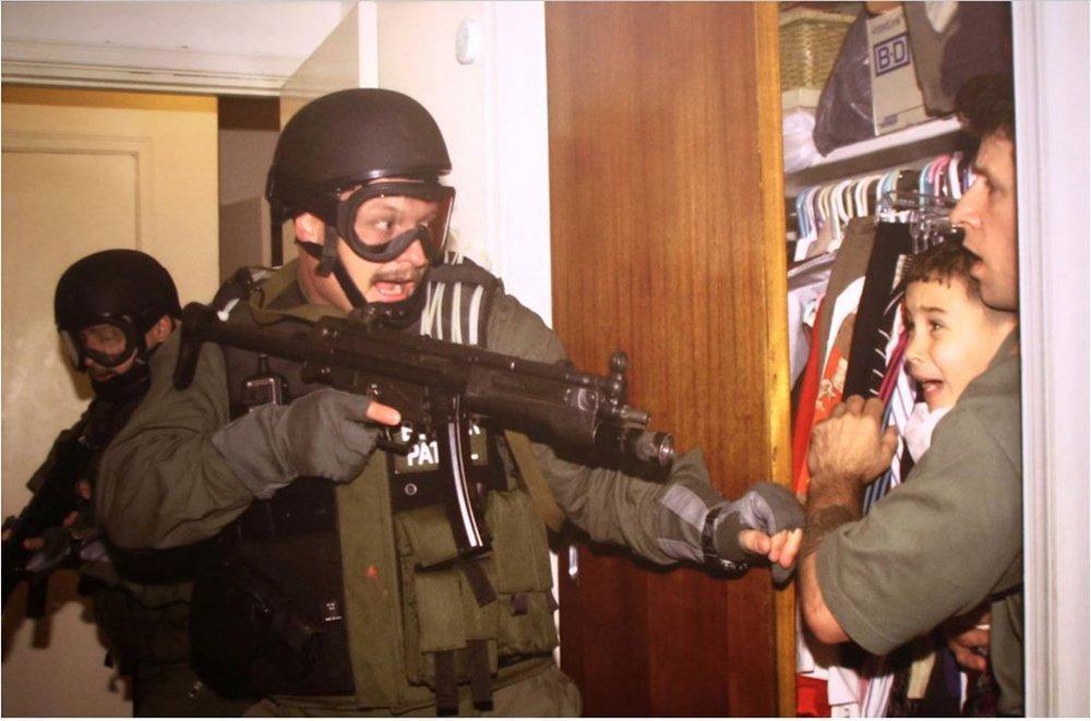 Agentes federales norteamericanos armados apoderándose de Elián González en la casa de su familia en Miami. (Crédito: Flickr)