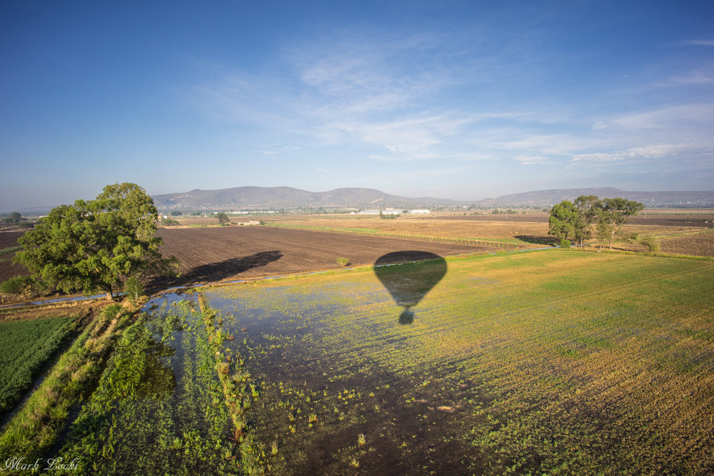 The hot air balloon casts a shadow over the farmers fields