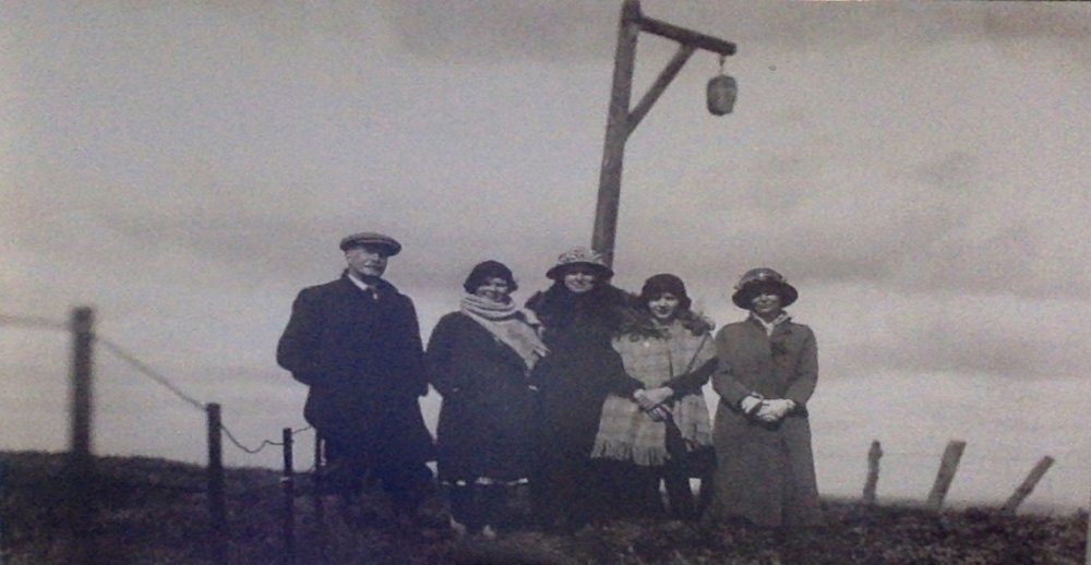 Negative from photograph of ''Winter Gibbet'' with five people standing before it.  Elsdon, Northumberland. nd. [c.1910]. Image courtesy of Northumberland County Archives service under Creative Commons Licence
