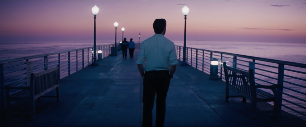 A trailer screen grab of Gosling walking along a pier, singing, towards a pastelly pink-purple dusk.