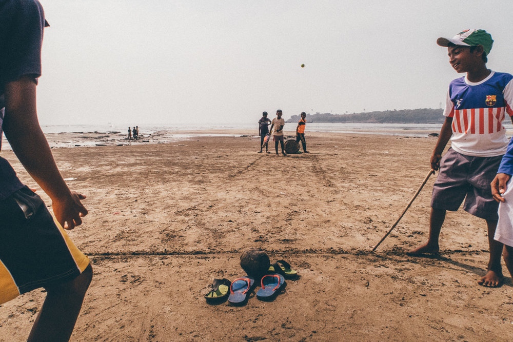 The sun's heat doesn't affect kids who play cricket. Versova Beach, Mumbai