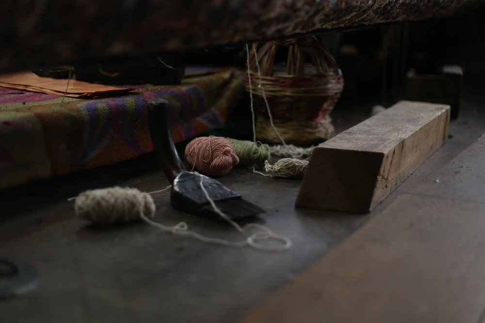 A view of balls of wool, lying next to a loom
