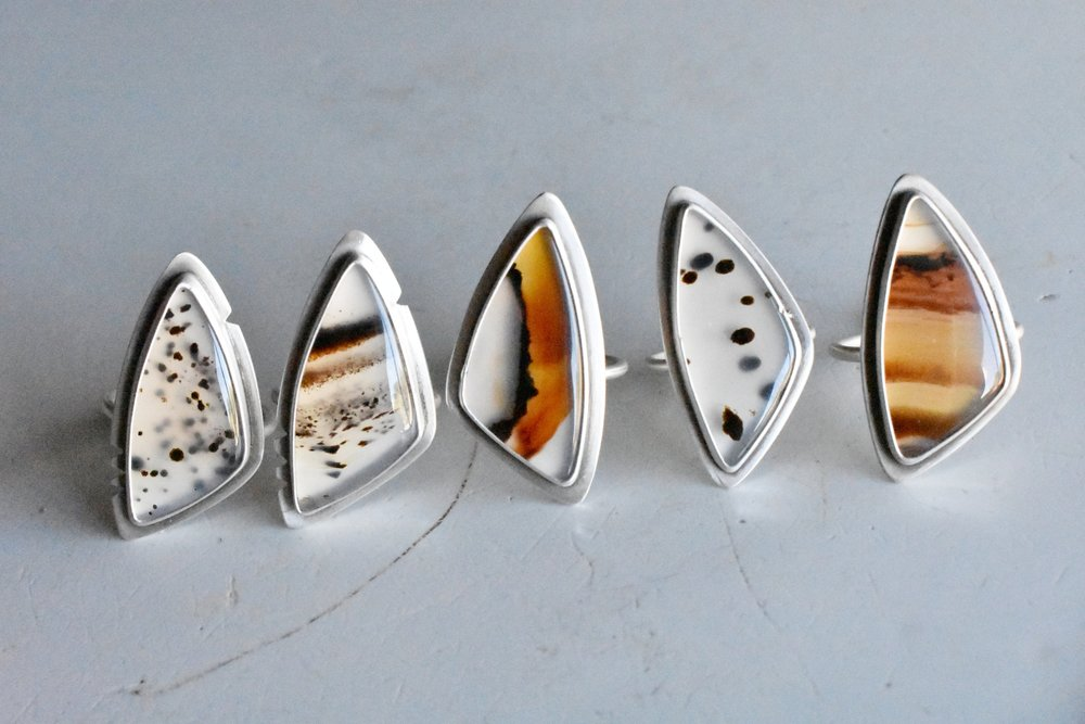 Bridger Rings - The medium size Montana agate rings, each stone and ring is unique. Montana agate is characterized by big sweeping lines of color with patches of dendritic manganese.Wholesale Price: $ 72.50Retail Price: $145.00
