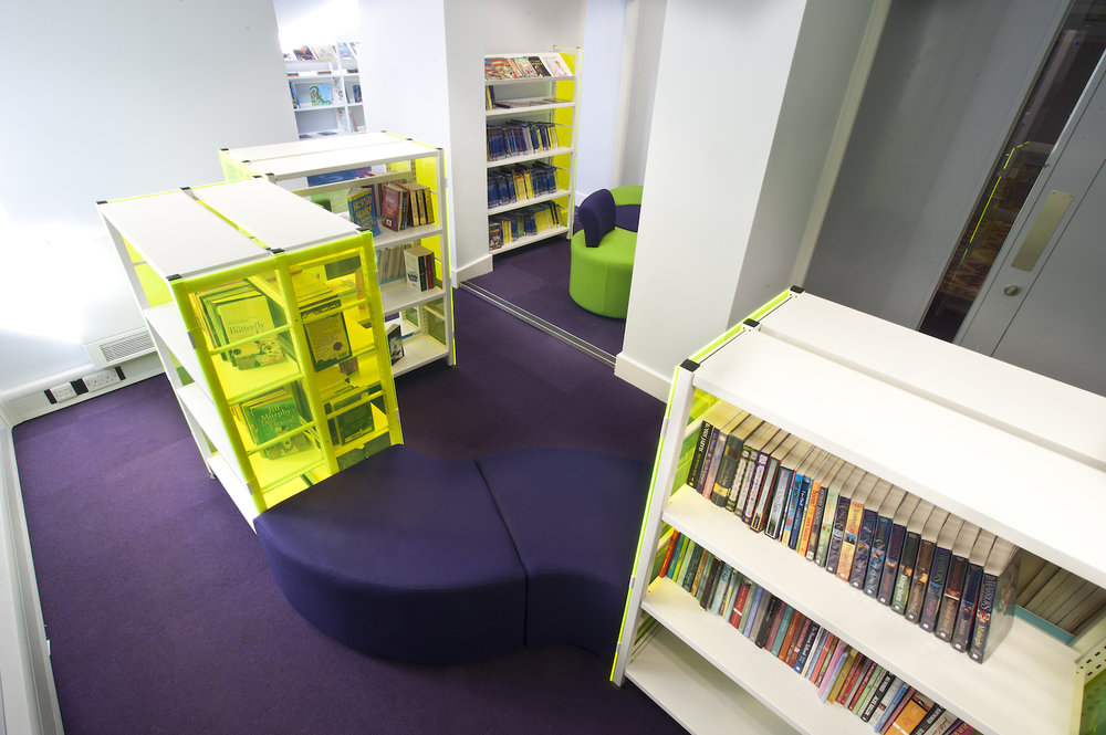 Soft seating pads positioned at an angle between shelving bays.