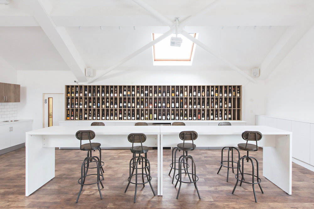 London tasting room with wine display, high level benches and fitted storage cupboards.