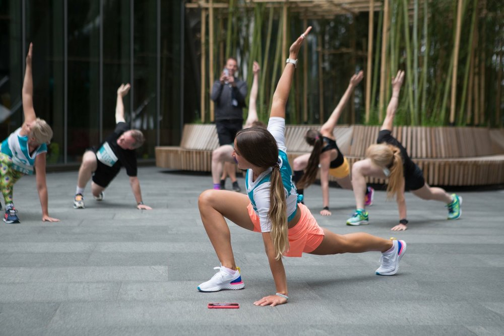 Grace taking a group through their warm up before Conquer the Tower for Trekstock