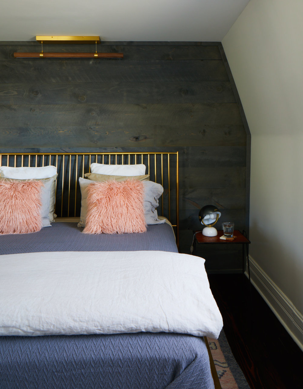 King bed in the Margaret Suite with fluffy pink pillows and brass headboard.