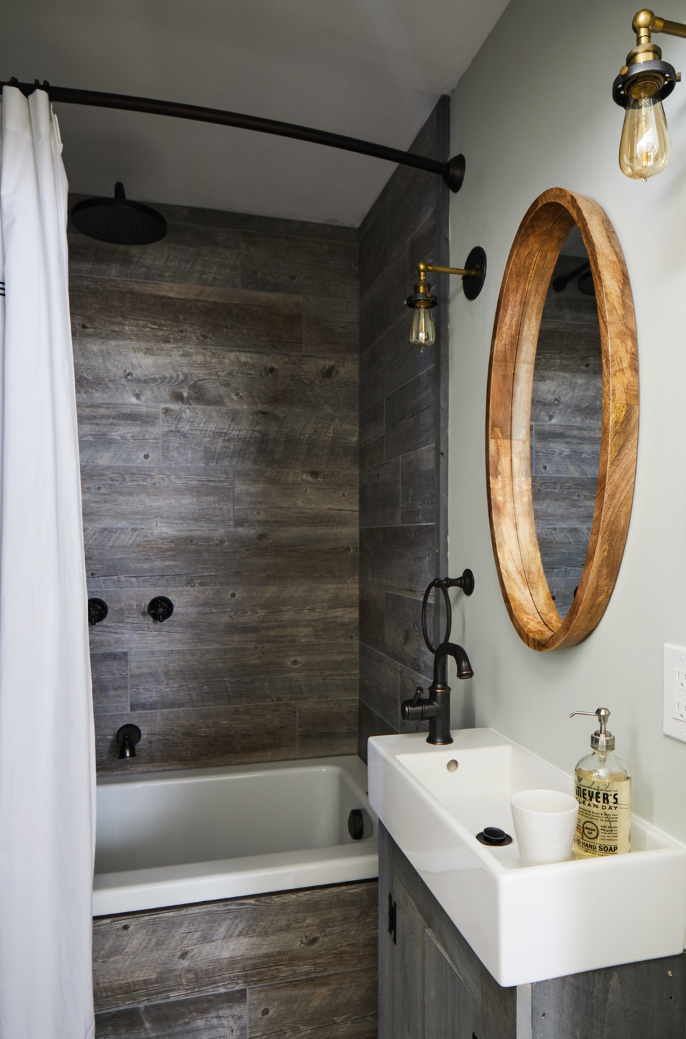 The Margaret Suite bathroom with wood paneling, white soaking dub and matching sink.
