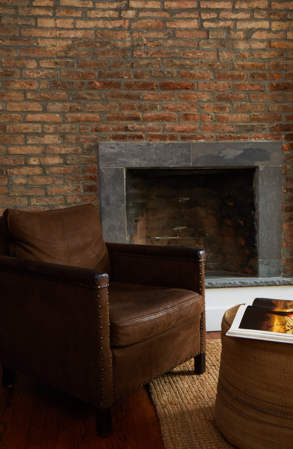 Arm chair and fireplace with reading material in the Half Pint.