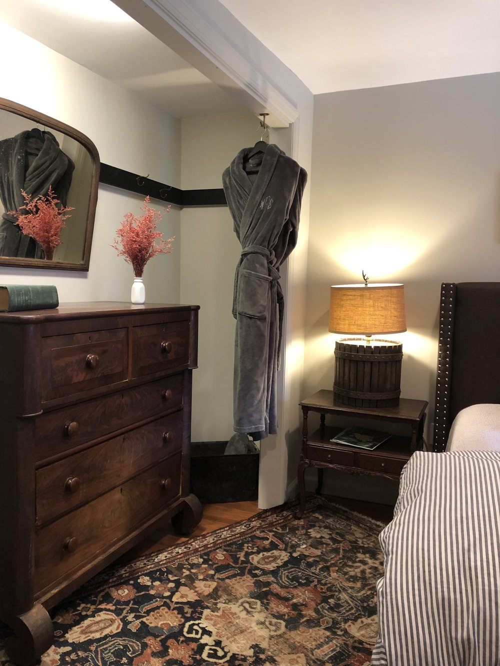 The Schooner Suite bedroom with antique rug and dresser, mirror and two plush robes.