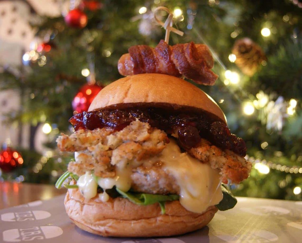 The Santa Special - Resting: Turkey patty, cranberry sauce, melted brie, spinach, sage and onion stuffing topped off with a pig in a blanket and served with Turkey Gravy on the sideRecommend with: Christmas Cocktail or a Smog Rocker Stout