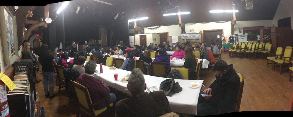 IMAGE DESCRIPTION: About one hundred people eat dinner around long banquet tables. Caption: a photo from a recent gathering of drivers and riders from the bristol county transportation network.