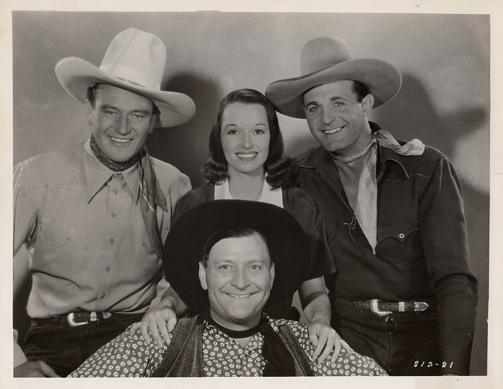 Louise Brooks, center, in Overland Stage Raiders (1938), in a still in which everyone but John Wayne looks a little unhinged.