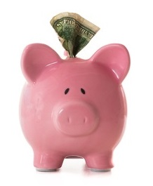 Piggy bank with paper money sticking out-Paid stock photo.jpg