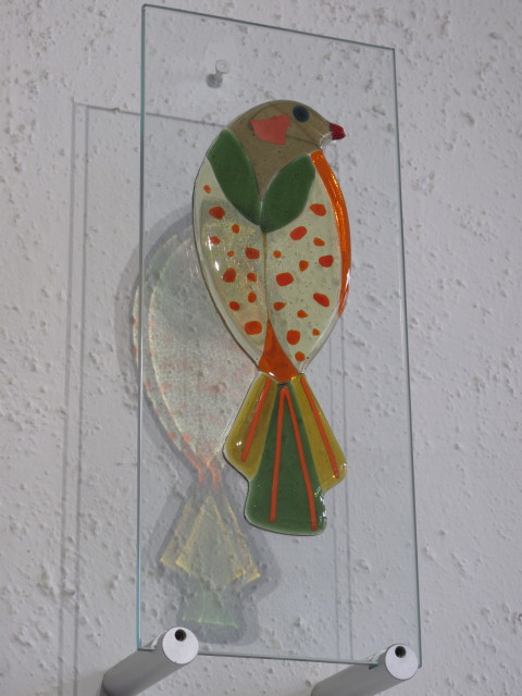 Green Bird- £150.00 (ex brackets)  -   ENQUIRE NOW     15cm x 37cm-    fused glass on clear glass pane   Each piece comes with it's own custom made wooden free standing base  The wall mounting brackets can be supplied for an additional cost