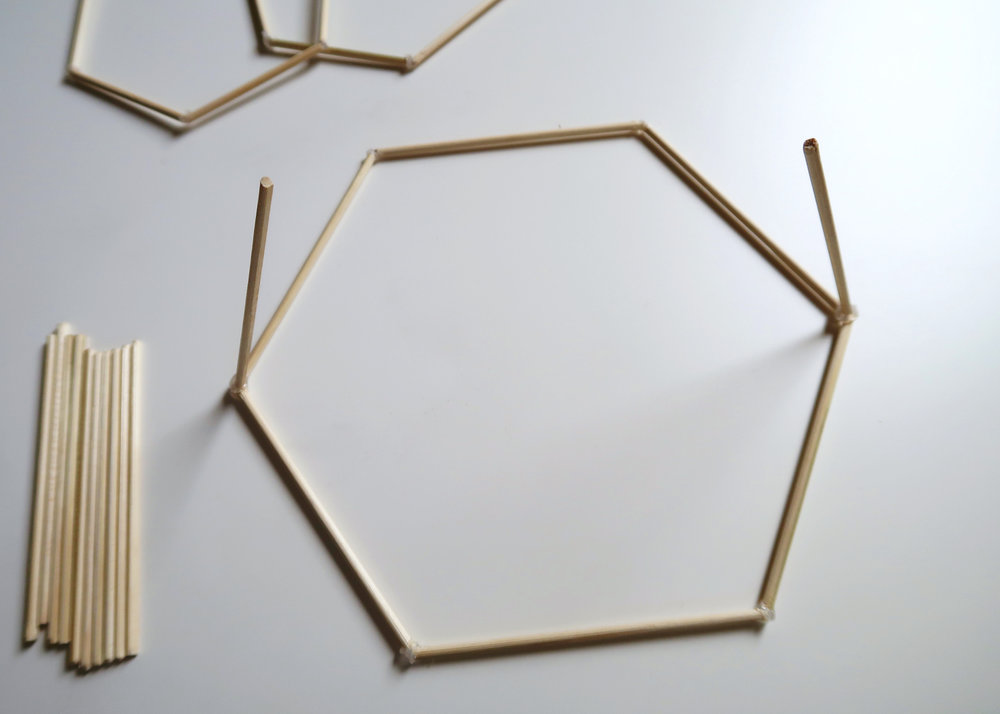 6. - Place the large hexagon flat and stick two of the 10cm skewers to opposite corners with hot glue, angling them slightly inwards as you do.