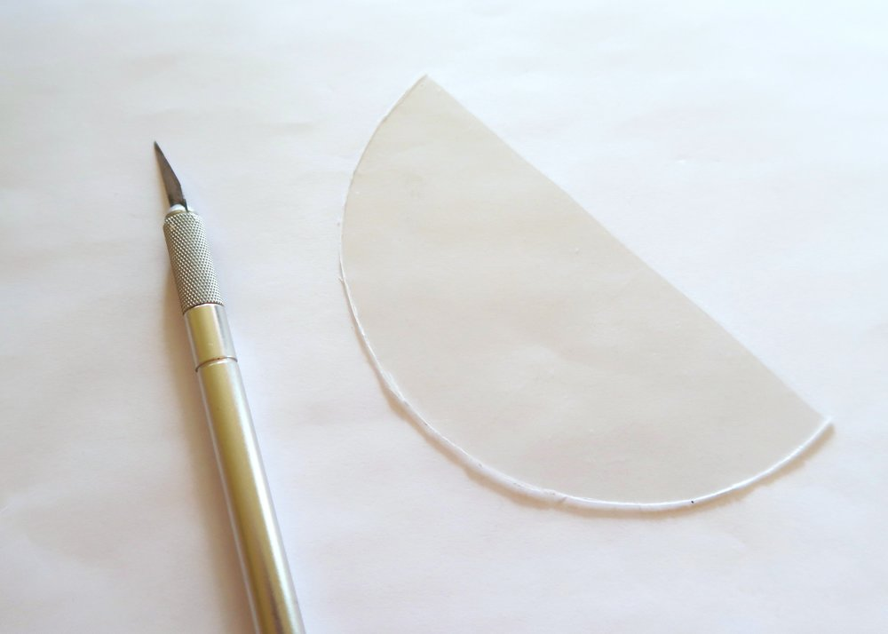 1. - First, draw out a semi-circle shape on a sheet of clear shrink plastic. Once you're happy with how it's looking, carefully cut it out using a craft knife or pair of scissors.