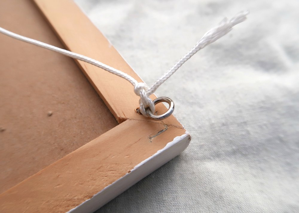 5. - If you want to hang your pin board, when the frame is dry, turn the board over and put two screw-in closed hooks into the top two corners of the pin board. Tie some strong string with a knot to one hook and then tie it at the other end to the other hook.