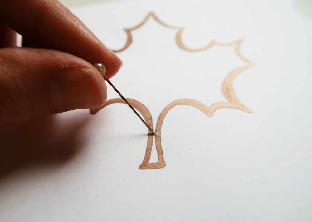 1. - First of all, you'll want to draw an outline of a leaf to use as a template on a piece of card. Next, push a pin through the stem of the leaf template to create a hole.