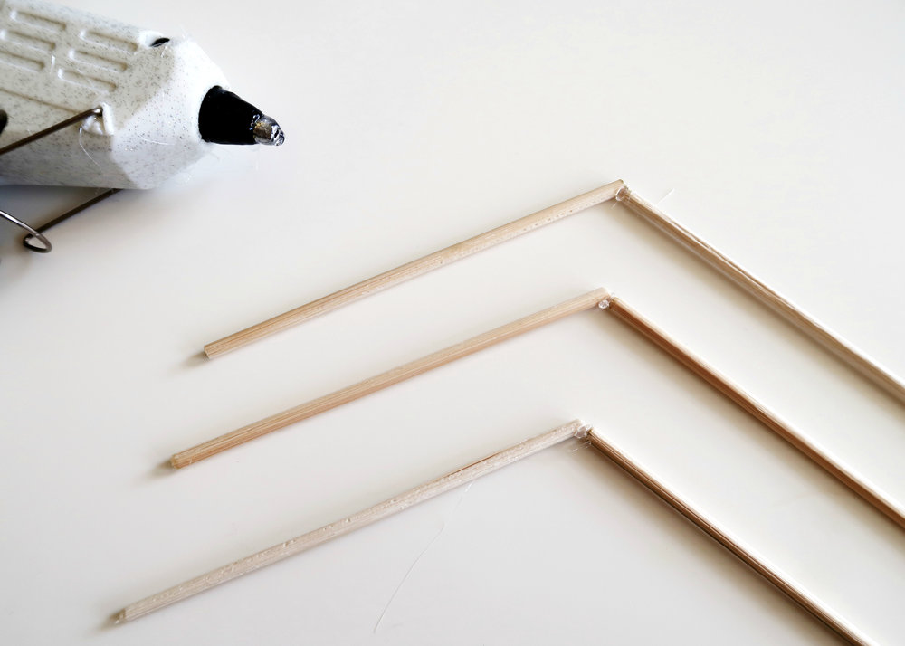 5. - Next, take your skewers and cut them so that you have 6 x 10cm lengths. Using the hot glue gun, stick 2 together at a time so that the interior angle is approximately 120 degrees.