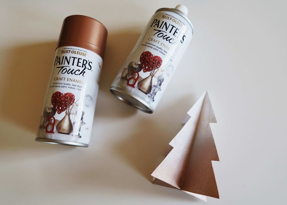 6. - When the copper paint is dry, now hold the tree by it's base (where you sprayed copper) and spray paint the top white.  Again, to get a gradient effect, start spraying off of the tree before moving down onto the tree and releasing pressure on the can (and moving the can away) as you do.