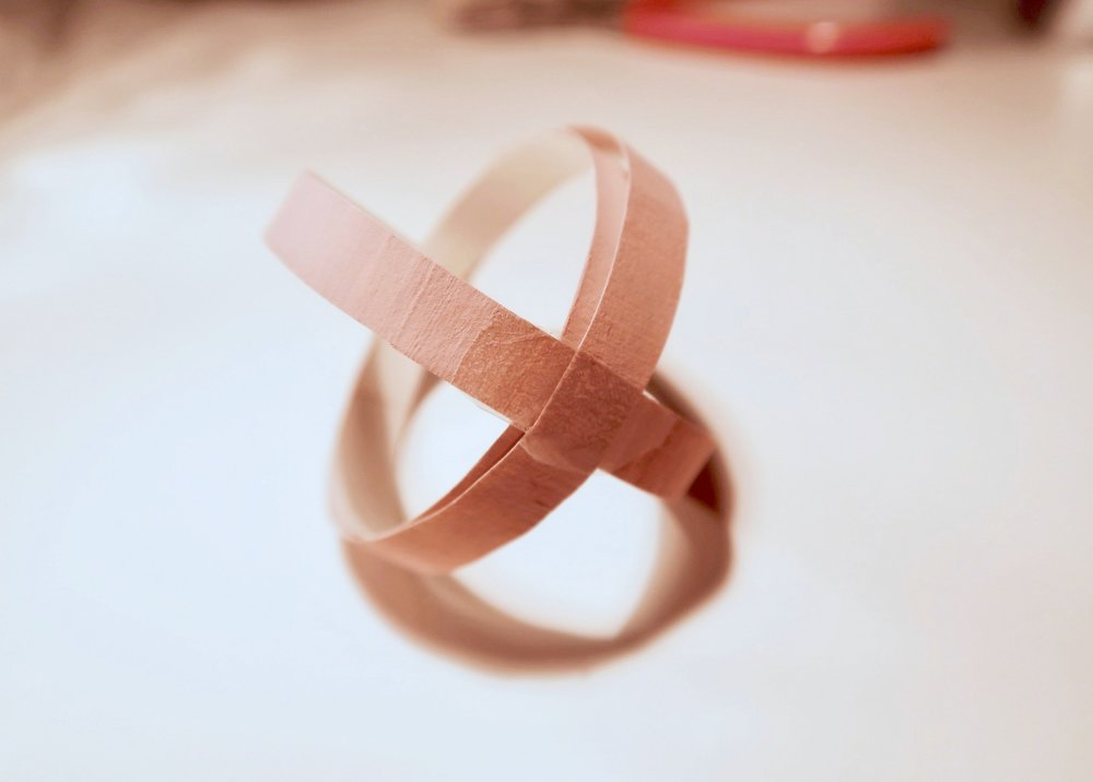 8. - Now the loops are secured together, seperate the outer two loops and position them so that they are perpendicular (form a cross from the top). Use some tape where they cross (opposite the headpin/loop) to fix them in place.