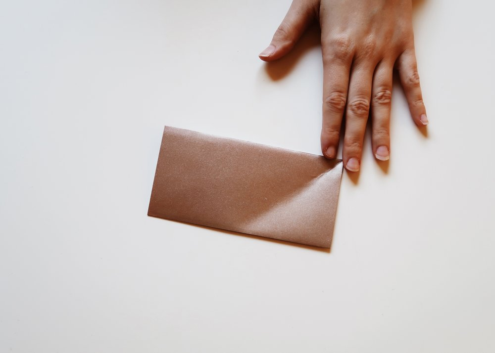 1. - If it isn't already, cut your paper so that it is a perfect square. Next, fold the paper in half so that the coloured side is on the outside.