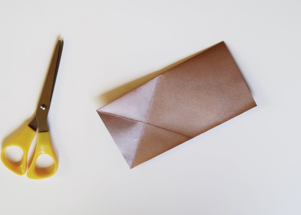 2. - With the fold at the top, take the bottom left corner and fold it so that the left side of the paper meets the top. Score and unfold. Repeat this with the top left corner so that the left side meets the bottom (open) side. Score and unfold.