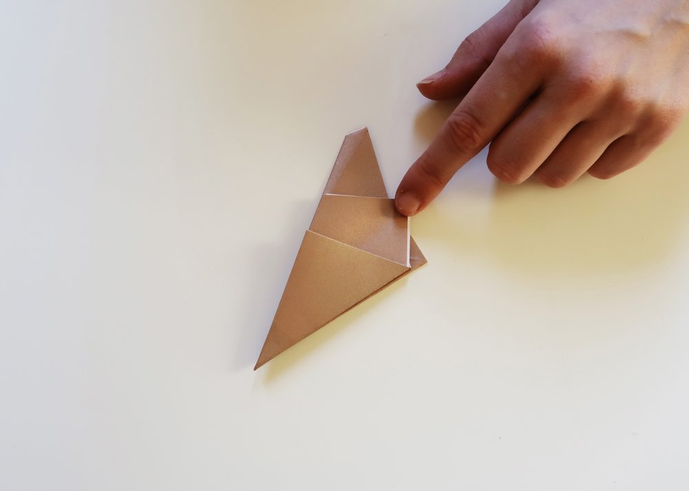 6. - Turn the paper over and fold in half so that you end up with a multiple-layered and almost-triangle shape.