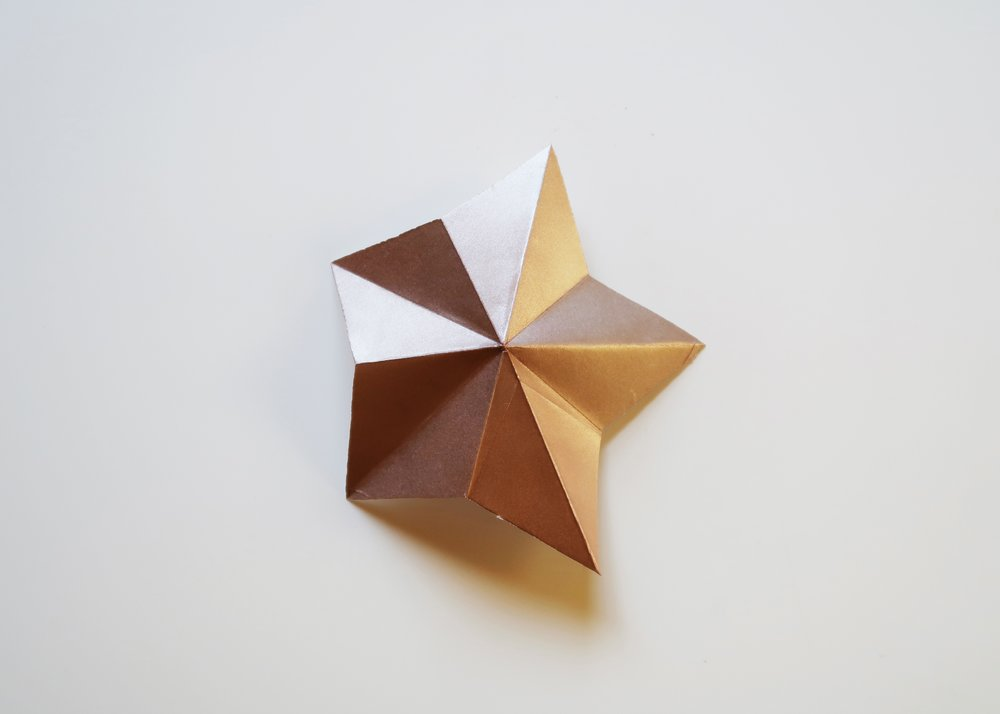 8. - Reinforce the folds on each point so that the points of the star stand up towards you whilst the folds in between go away from you. Finally, stick to your wall with masking tape to create a starry backdrop!