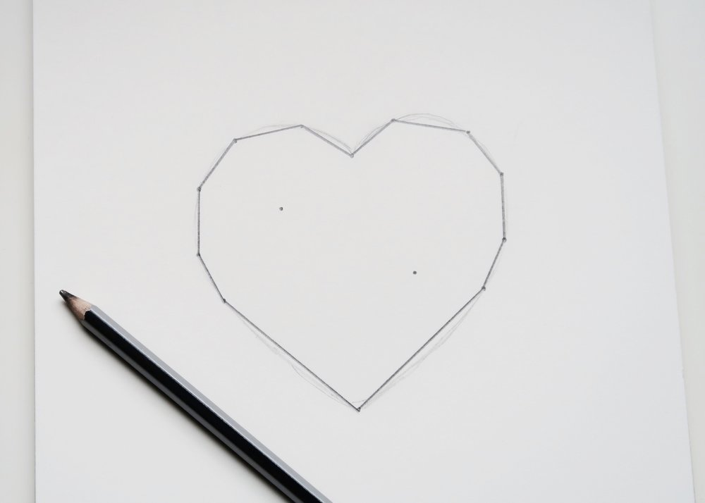 1. - First of all, draw a heart shape in the centre of a piece of paper. Next, mark points around the heart to simplify it whilst still looking like a heart. Join these points together using straight lines and then put two points inside the heart.