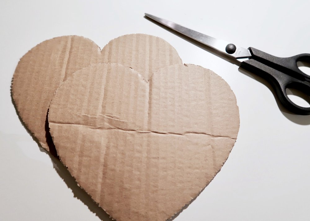 1. - First of all, cut out two heart shapes from cardboard. I used a template to make sure my shapes were identical. These will form the top and bottom of your pinata.