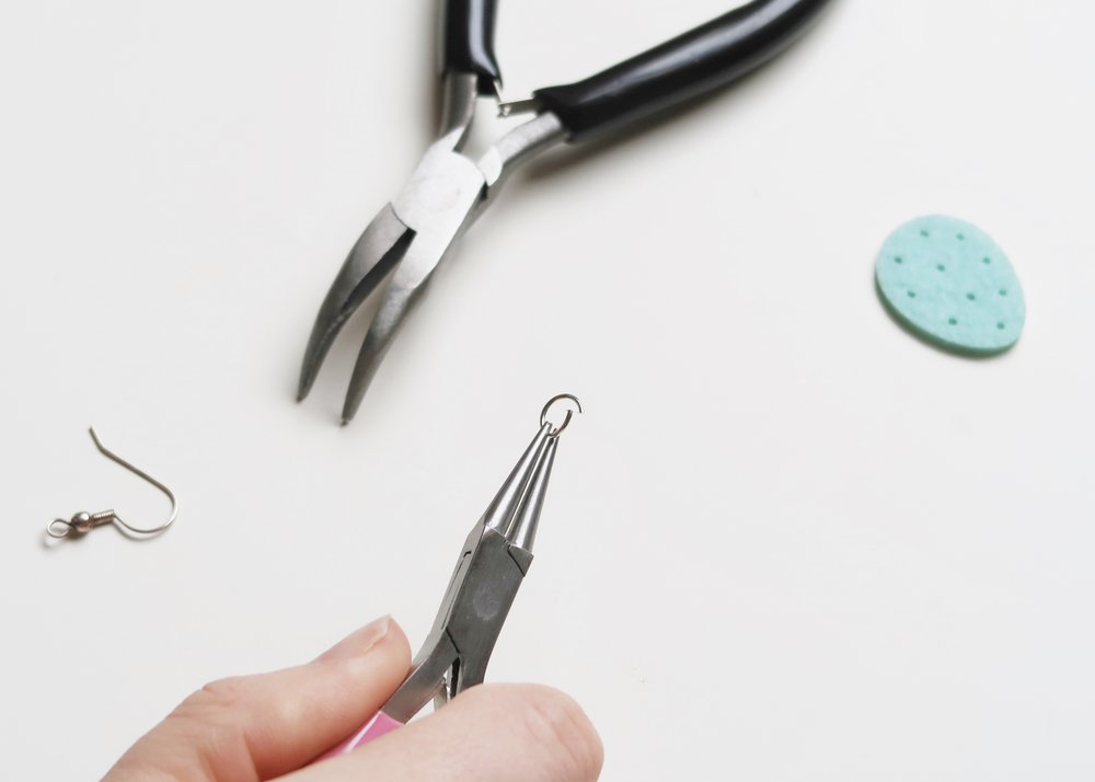 2. - If your confetti doesn't already have holes in, place it onto a rubber and use a pin to carefully create a hole in it. Use the pin to widen the hole. Next, open up a jump ring using pliers by twisting one side of the jump ring in the opposite direction to the other.