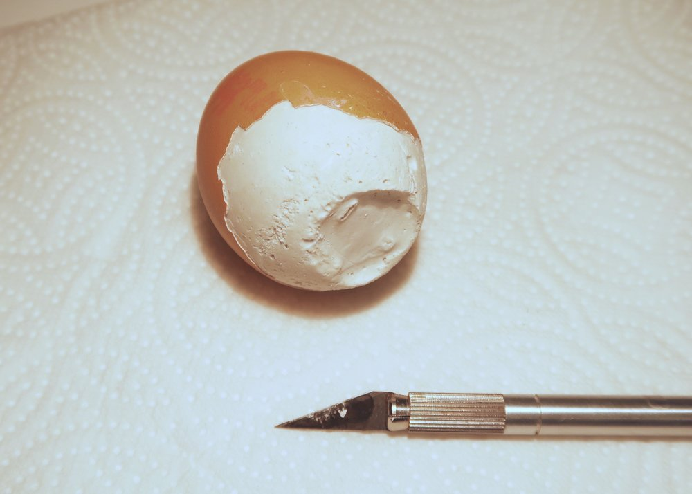 3. - When the exposed plaster feels dry, use the end of the craft knife to tap all over the egg shell so that cracks develop all over. Next, use the blade of the craft knife to carefully peel the shell away from the plaster.