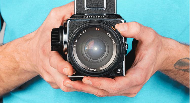 Foto von einer Person, die eine Kamera zeigt, illustriert Ihre Vision und Ihre Entscheidungen, um Artikel auf eBay zu fördern, um Provision zu verdienen.