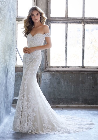 Morilee 8203  has intricate lace and delicate off-the-shoulder sleeves.