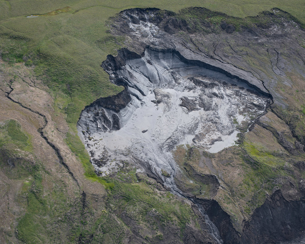 Deformed glacier ice revealed in the headwall of a thaw slump, slurry draining towards the sea below