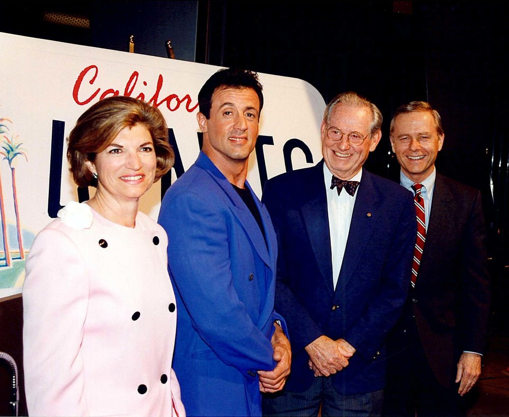Joanne KozbeRg, THEN-director of the California Arts Council; Sylvester Stallone; Wayne Thiebaud; and Governor Pete Wilson launched the California Arts Plate program on April 29, 1993 at the Warner Bros. Studios in Burbank.