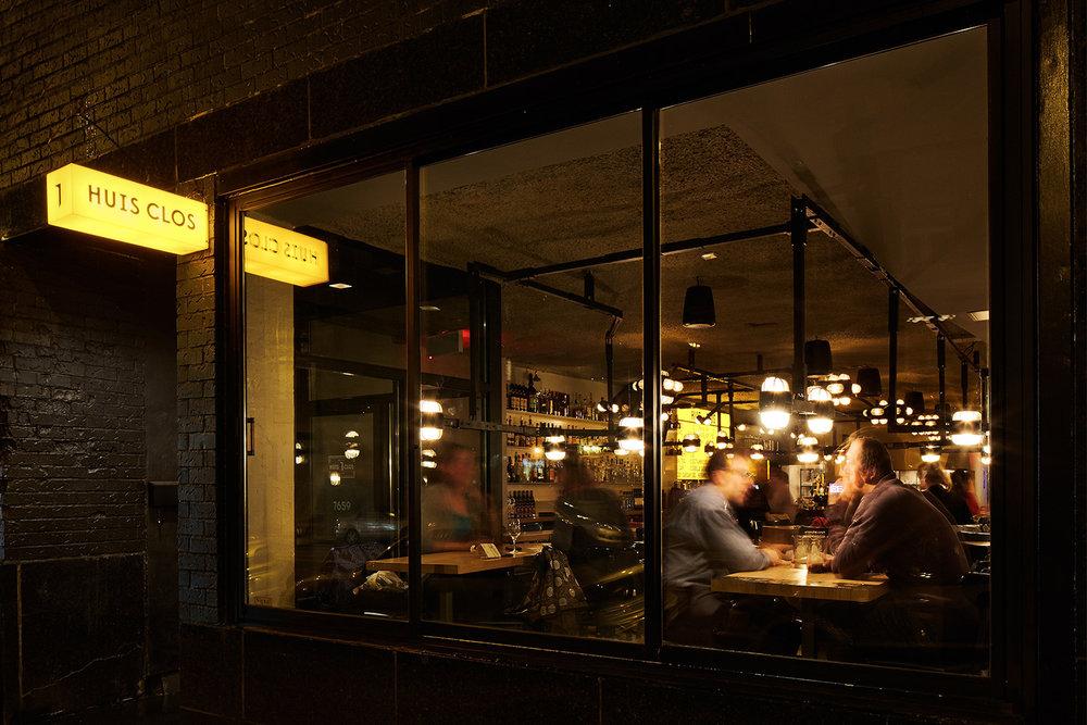 Vue de la vitrine de la salle à manger du restaurant Huis Clos. Enseigne rectangulaire jaune rétro-éclairée. Clients discutant sous un luminaire sur mesure suspendu d'apparence très mécanique