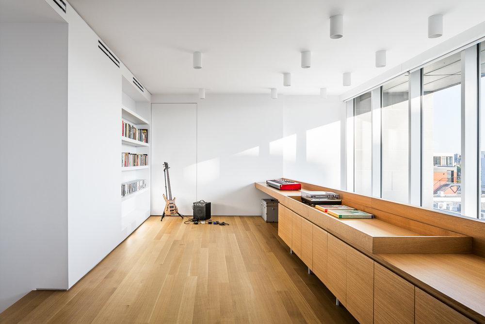 Salle de séjour sur mezzanine avec plancher et mobilier fait en chêne blanc. Luminaires cylindriques blancs en surface du plafond. Bibliothèque blanche