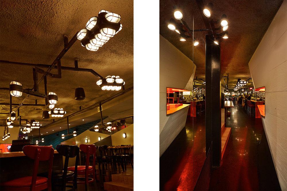 Luminaires custom fait de tubes d'acier très industriel suspendus pour créer des groupes de lampes au dessus des différentes zones du restaurant. Le mur de la cuisine en bois texturé peint blanc.