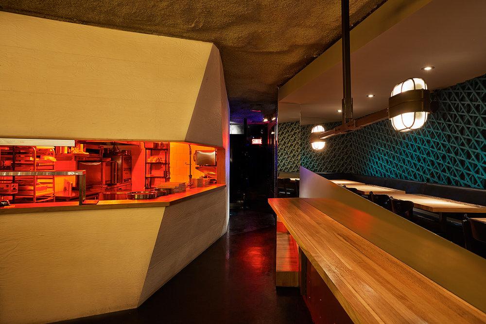 La cuisine et de la salle à manger, 2 volumes distincts. La banquette est entourée d'un treillis géométrique turquoise. Le bloc cuisine, ouvert au centre laisse entrevoir un éclairage plus chaleureux