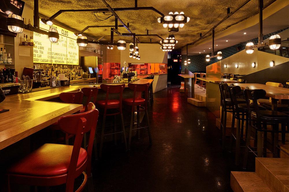 Vue du bar avec luminaires industriel suspendus au-dessus des différentes zones. Menu fait d'un tableau d'affichage jaune avec lettres vintages. Chaises de salle à manger transformées en tabourets