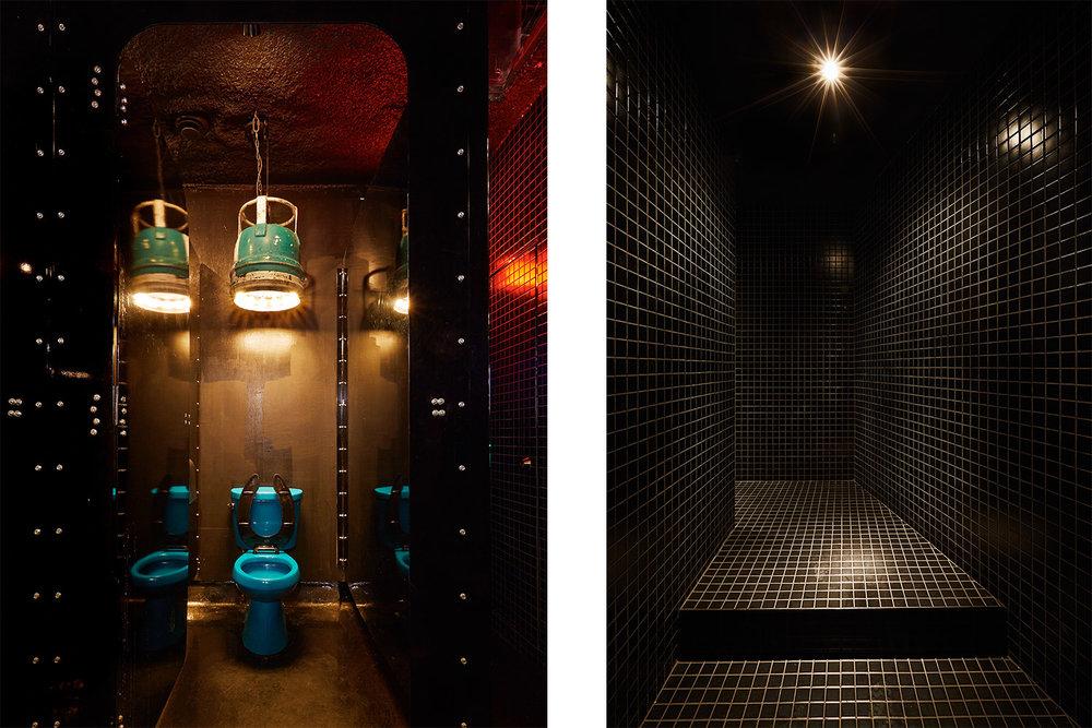 Salle de bain avec cabines noir lustrée. À l'intérieur une toilette bleu et un luminaire suspendu fait à partir d'une ancienne bouée marine. Adjacent un couloir fini avec de la mosaïque noire