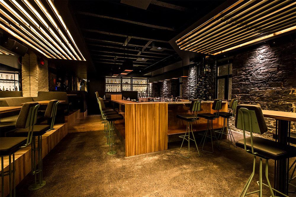 Salle à manger du restaurant avec murs de pierres d'origines et plancher de béton poli. Les lampes custom surplombent le comptoir bar fait en bois de hêtre. Tabourets en feutre et peint vert-de-gris