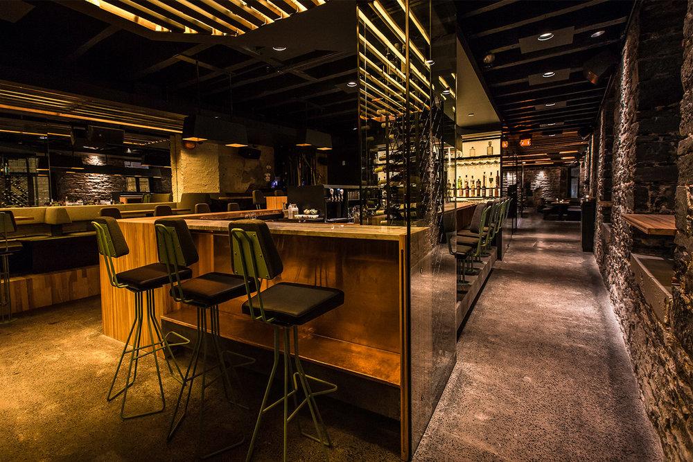 Vue du bar avec murs de pierres d'origines et plancher de béton poli. Le comptoir, fait de bois de hêtre, de cuivre et de marbre, entouré de tabourets custom fini en feutre et peint vert-de-gris
