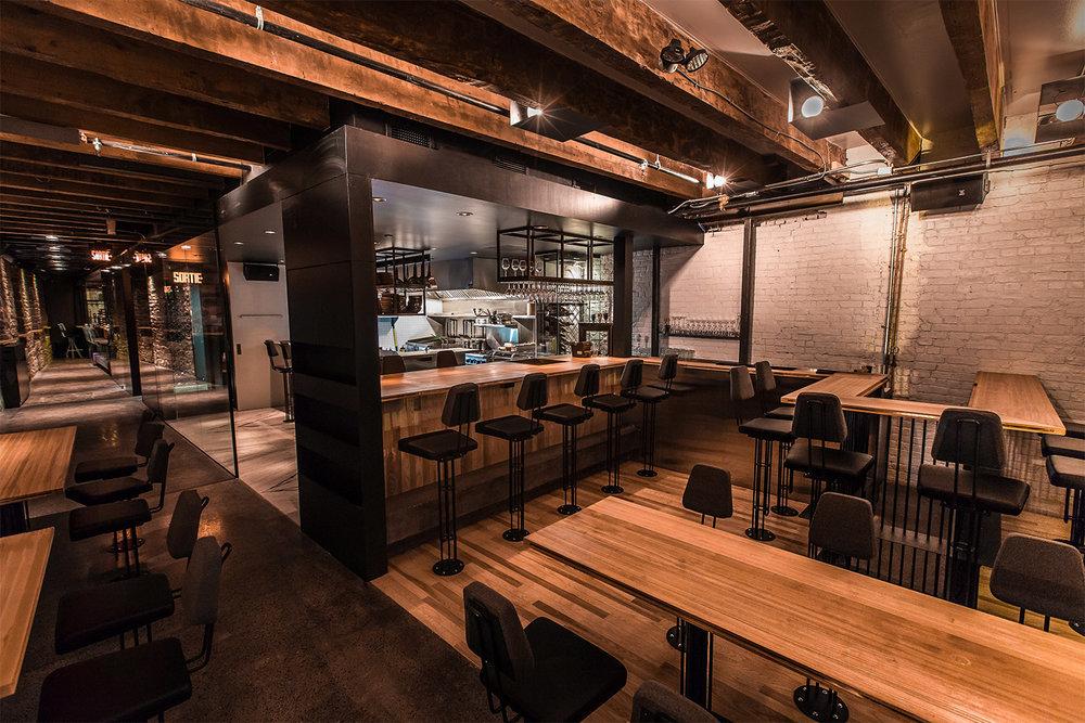 Cuisine du restaurant avec mur de briques blanc. Plusieurs finis de plancher dans cette zone : bois de hêtre, béton poli et de marbre statuario. Une paroi de verre sépare le couloir de la cuisine